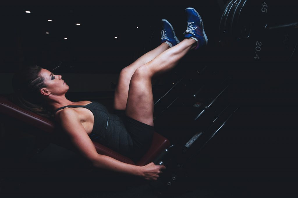 girl lifting weight on leg press